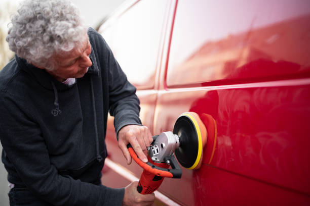 Polishing a car with electric orbital polisher stock photo