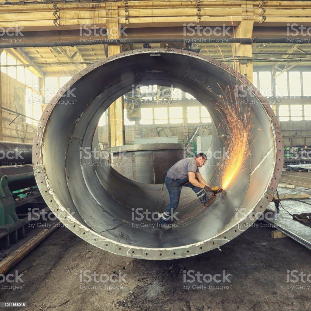 Worker grinding inside of large metal cylinder.