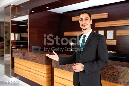 Polite receptionist welcoming hotel guests with an honest smile
