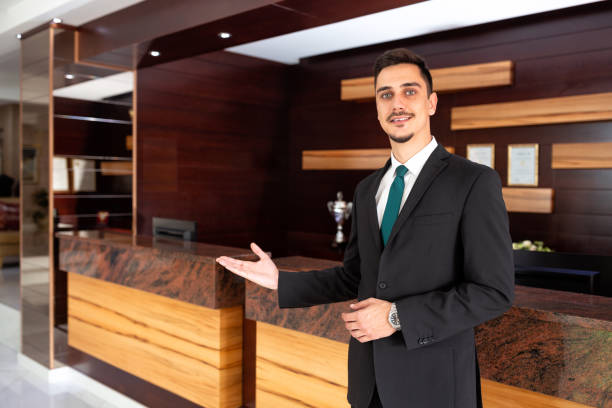 Polite receptionist welcoming hotel guests stock photo