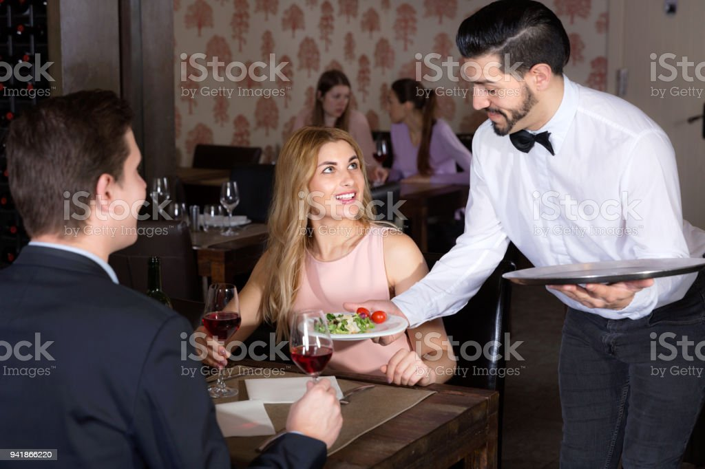 Polite waiter bringing ordered dishes to smiling couple at restaurant stock photo