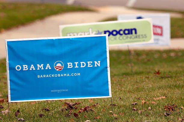 """Political Campaign 2012 Yard Signs """"Madison, Wisconsin, USA - November 3, 2012: An Obama Biden 2012 presidential campaign yard sign in the foreground along with a Mark Pocan for Congress and Tammy Baldwin for Senate on the lawn of a Madison, Wisconsin home."""" 2012 stock pictures, royalty-free photos & images"""