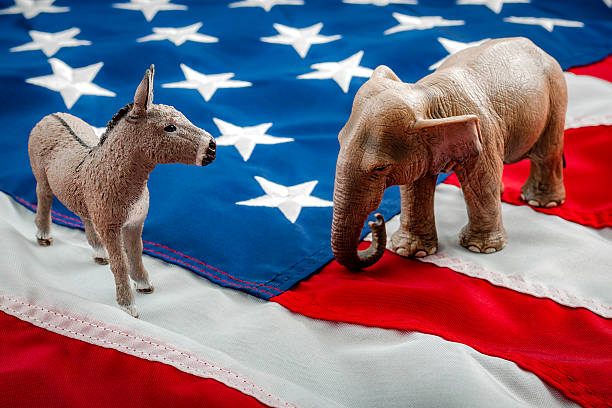 Political face off in November Democrats vs republicans are facing off in a ideological duel on the american flag. In American politics US parties are represented by either the democrat donkey or republican elephant political party stock pictures, royalty-free photos & images