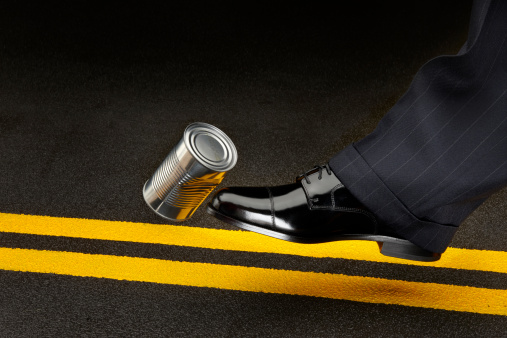 close up of politician's shoe kicking a dented shiny can down the road