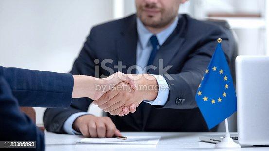 istock Politician of European Union signing sanction termination, congratulates partner 1183385893