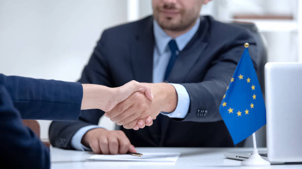 Politician of European Union signing sanction termination, congratulates partner Politician of European Union signing sanction termination, congratulates partner diplomacy stock pictures, royalty-free photos & images