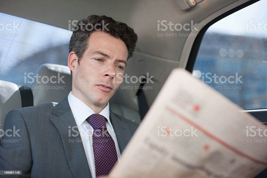 Politician reading newspaper in backseat of car stock photo