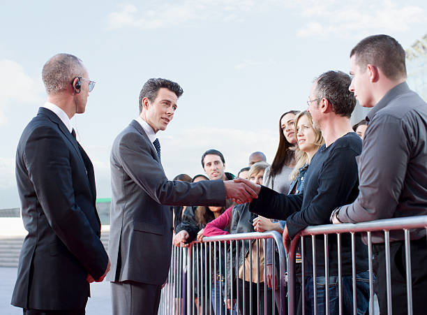 politician shaking hands with people behind barrier - politician stock photos and pictures