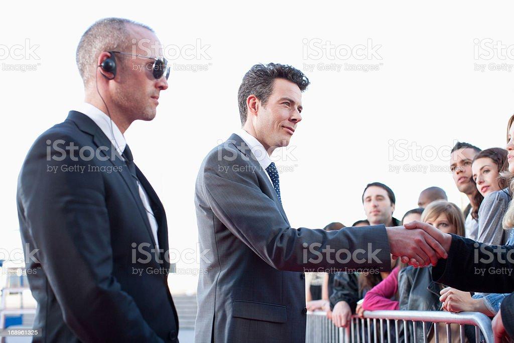 Politiker beim Händeschütteln mit Menschen, die hinter der Schranke - Lizenzfrei 25-29 Jahre Stock-Foto