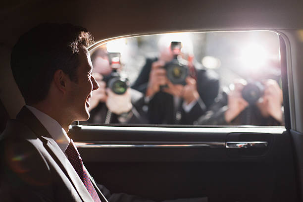 politician smiling for paparazzi in backseat of car - fame stock photos and pictures