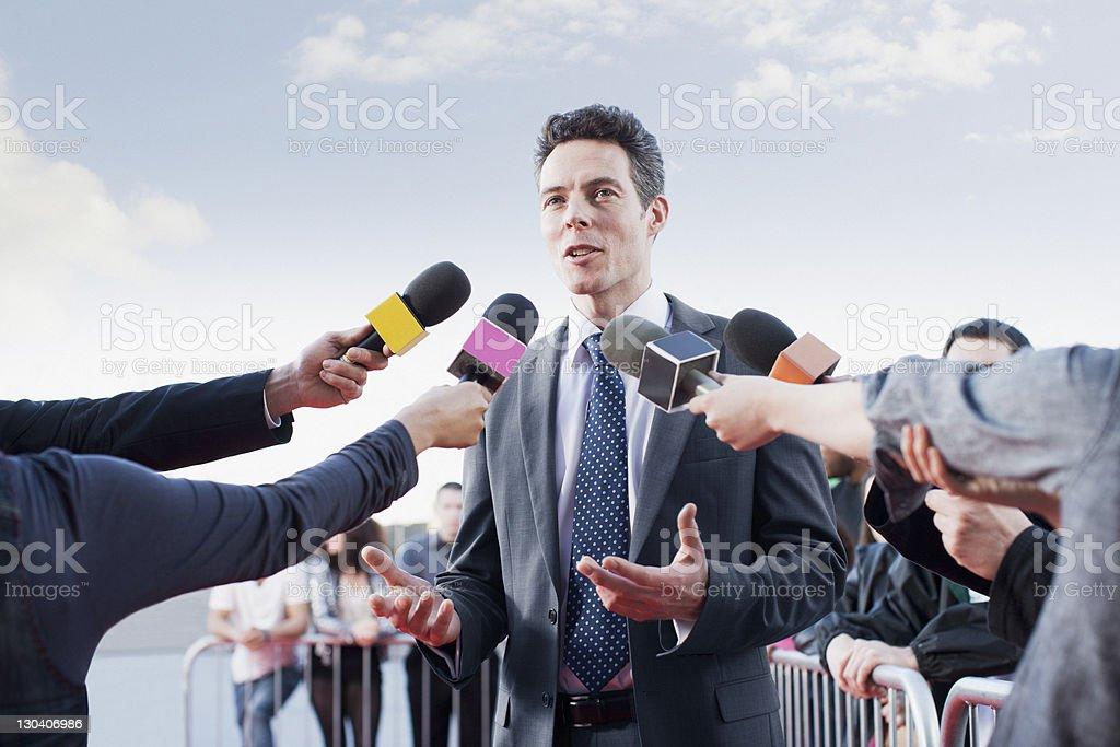 Político hablando en reporters'micrófonos - foto de stock