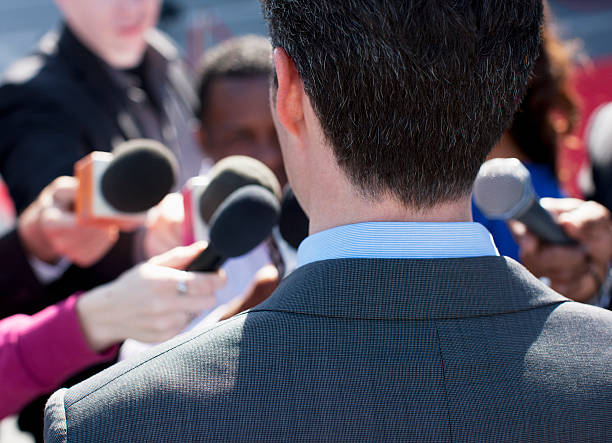 politician talking into reporters' microphones - politician stock photos and pictures