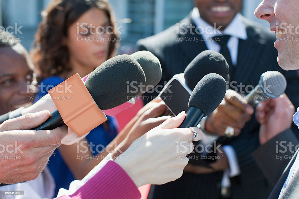 Politician talking into reporters' microphones stock photo