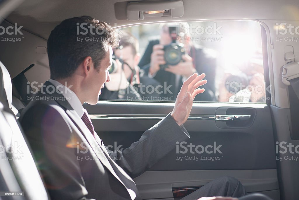 Politician waving from backseat of car stock photo