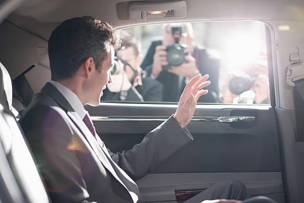 politique agitant de backseat de voiture - homme faire coucou voiture photos et images de collection