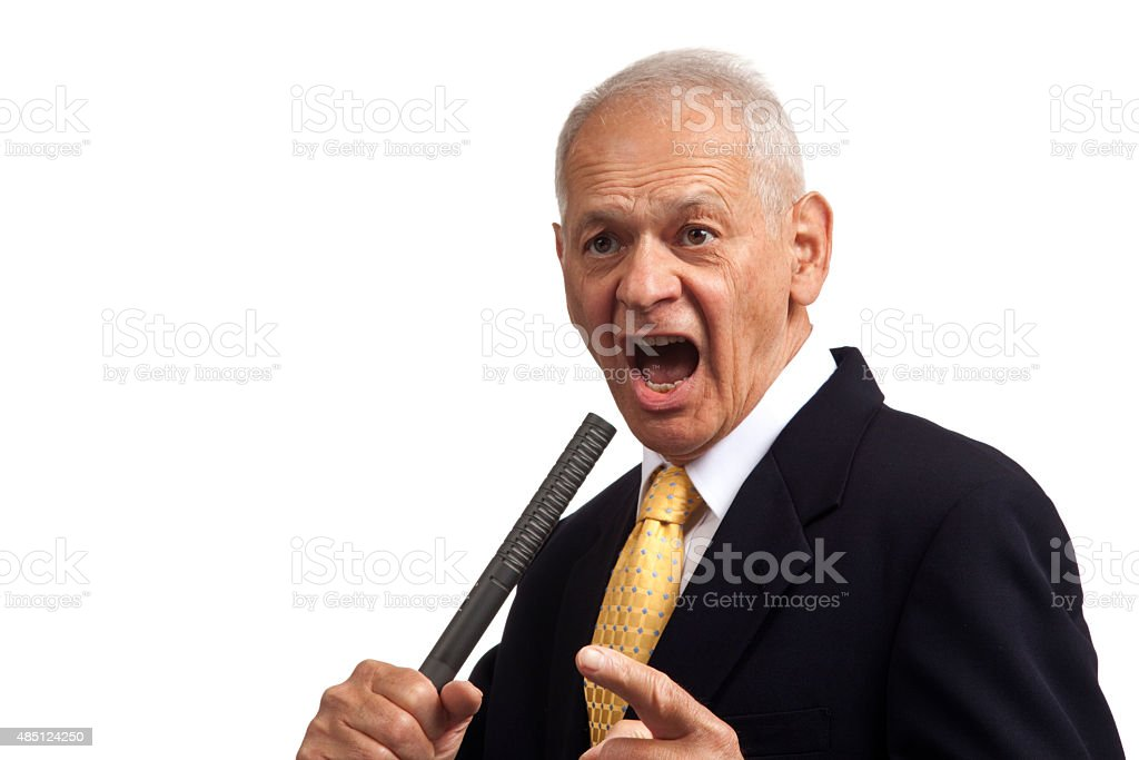 Politician with microphone yelling looking out at imaginary crowd stock photo