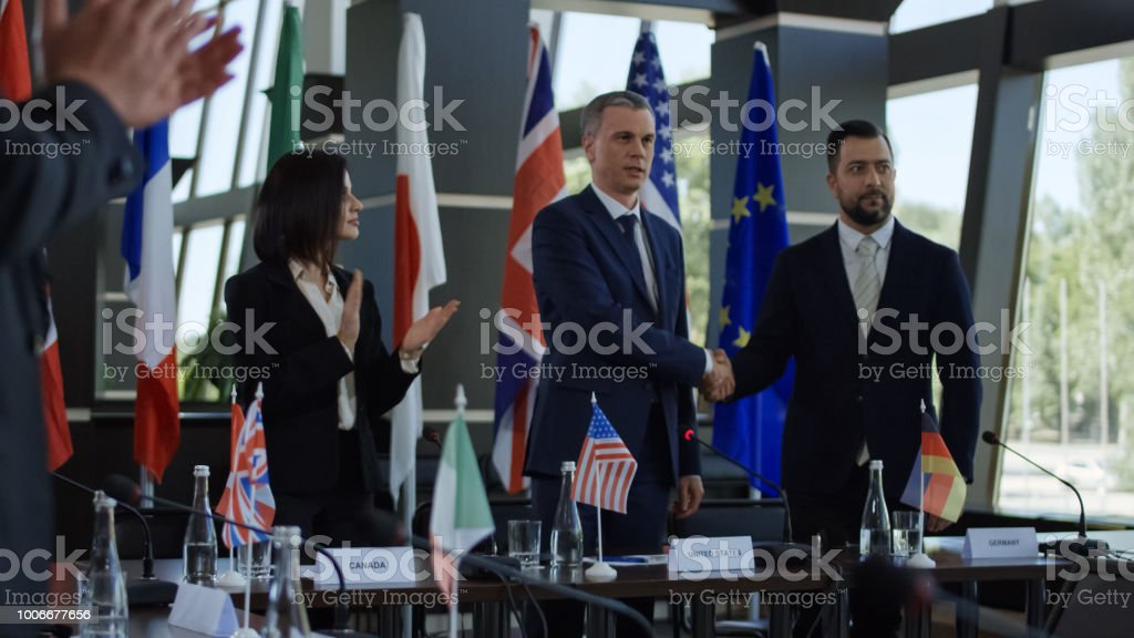 Politicians shaking hands in agreement on negotiation stock photo