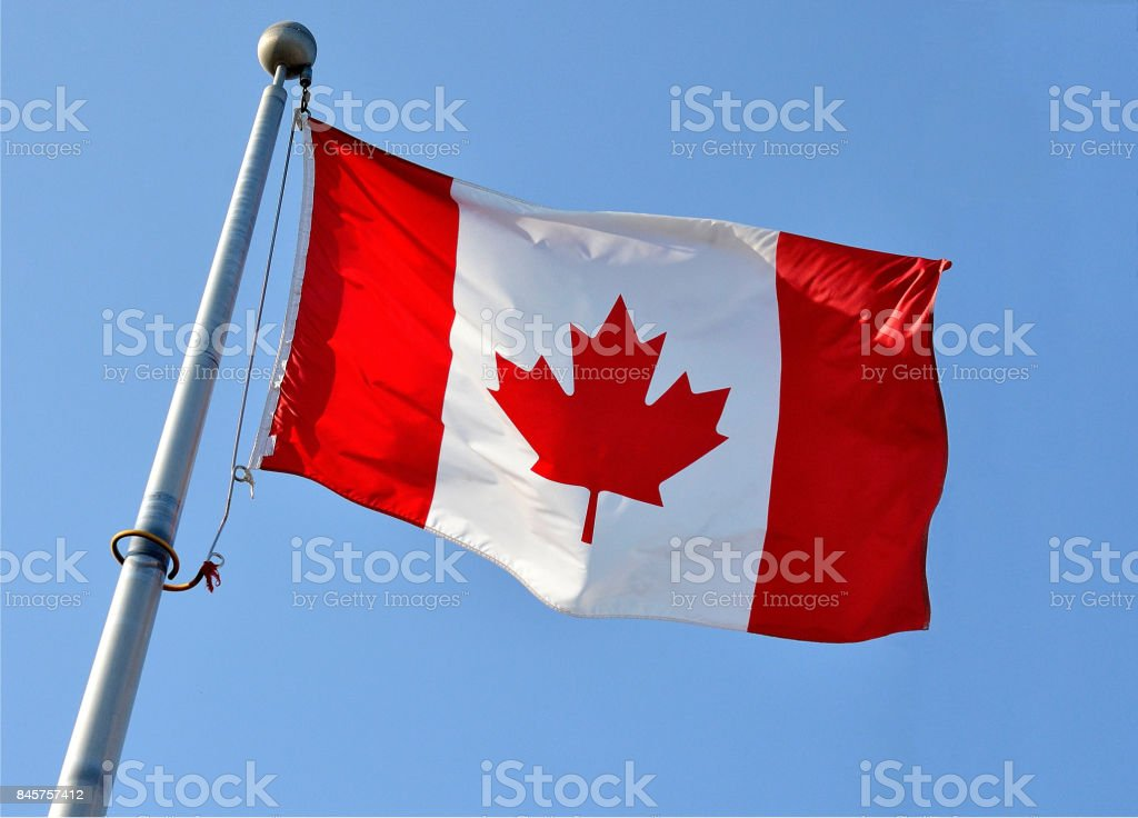A tight shot of a Canadian flag, flying in a bright blue sky, with no...