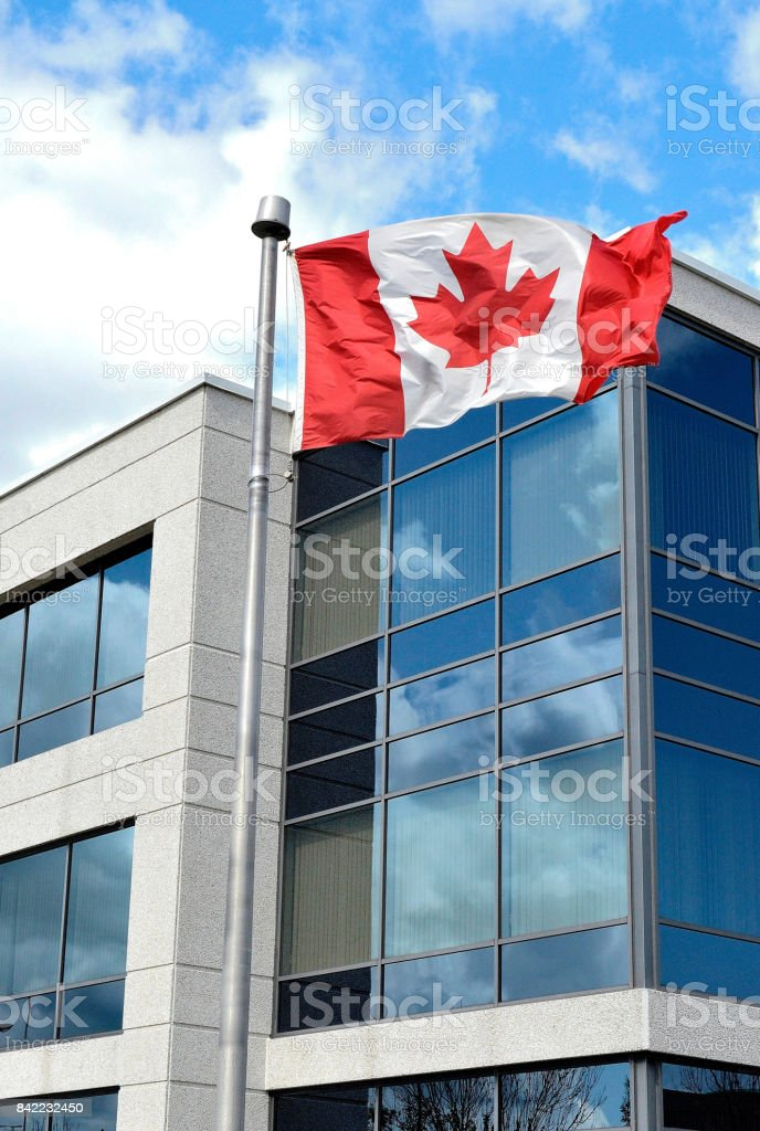 A Canadian flag waves in a bright blue sky, with a building behind.