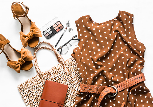Polka dot summer brown dress, suede wedge sandals, eco straw tote bag, cosmetics on a light background, top view. Women's clothing set