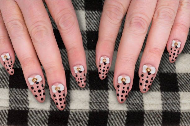 polkadot pink nail polish  with small bows Mature Woman showing her acrylic polkadot pink nails  with white bow and rhinestone on checkered woolen skirt pink nail polish stock pictures, royalty-free photos & images
