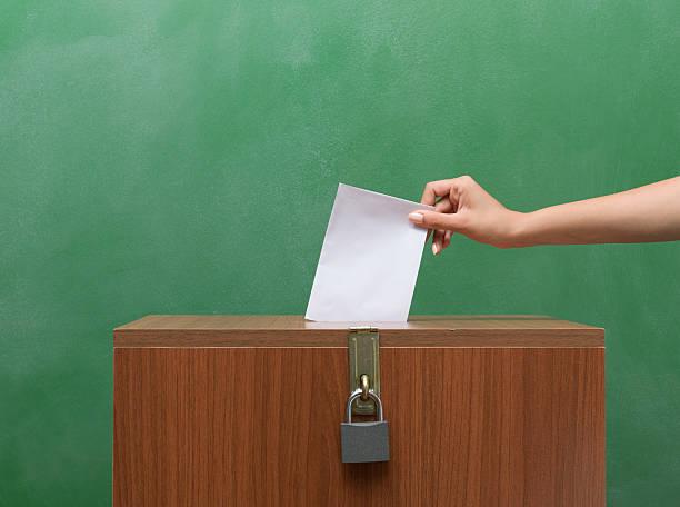poll envelope in human hand inserting to the ballot box - voting hands stockfoto's en -beelden
