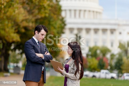 A young politician, staffer, or lobbyist stands and listens to a poll taker/political canvasser with his arms folder, wearing a posture of frustration.
