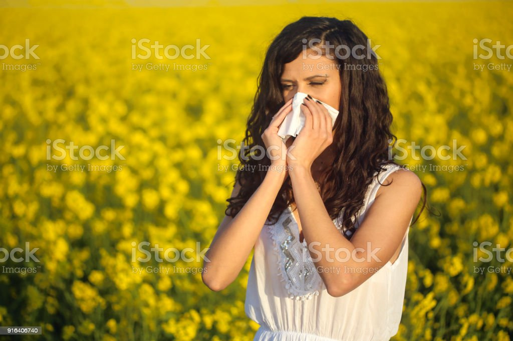 Young woman with pollen allergy, blowing her nose in a handkerchie....