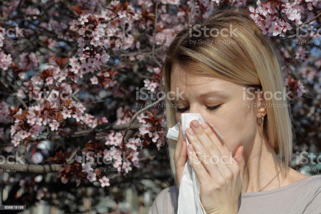Pollen allergy, Springtime. Woman sneezing in a tissue outdoors