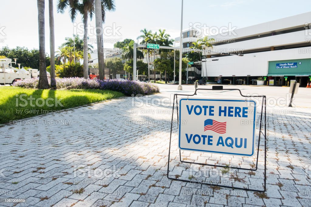 Polling Station Sign in Miami Beach in English and Spanish August 18, 2020 - Miami Beach, FL USA - Vote here sign in English and Spanish at a polling station in front of City Hall. American Flag Stock Photo