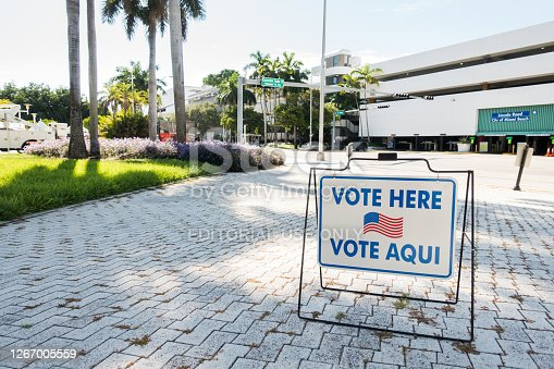 August 18, 2020 - Miami Beach, FL USA - Vote here sign in English and Spanish at a polling station in front of City Hall.