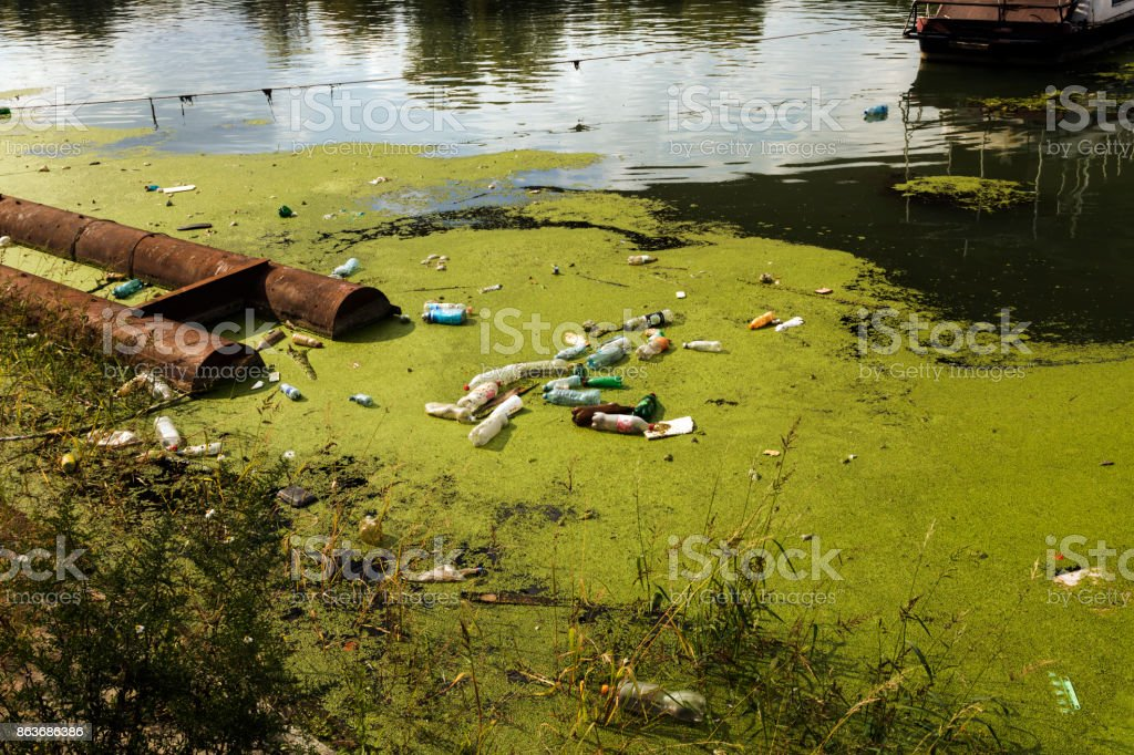 Polluted river full of various garbage stock photo