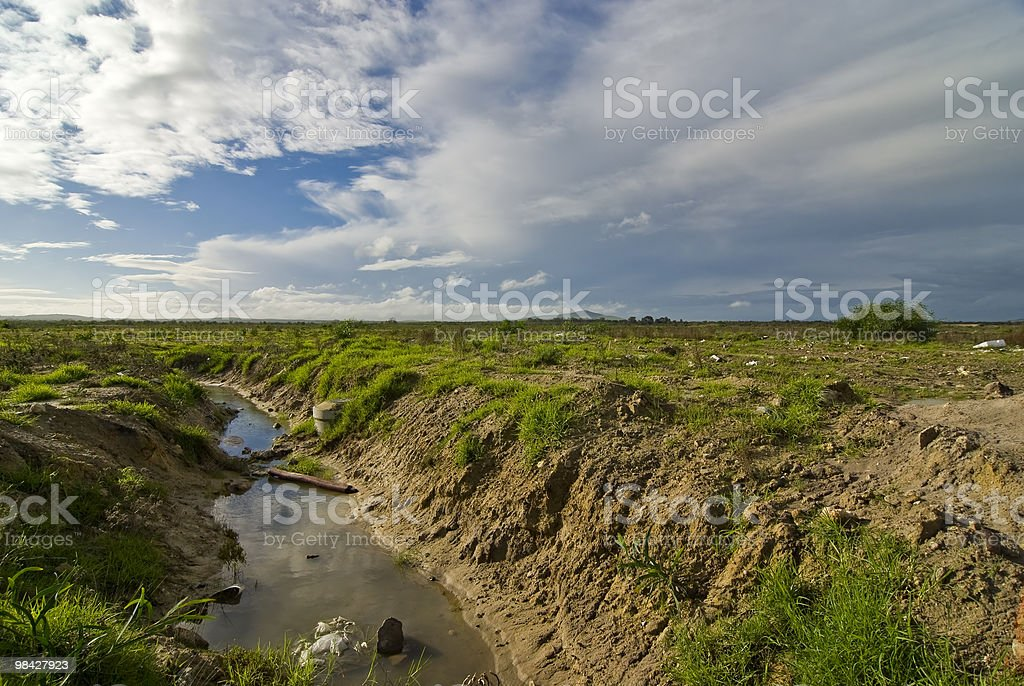 Polluted stream with landscape and blue skies royalty-free stock photo