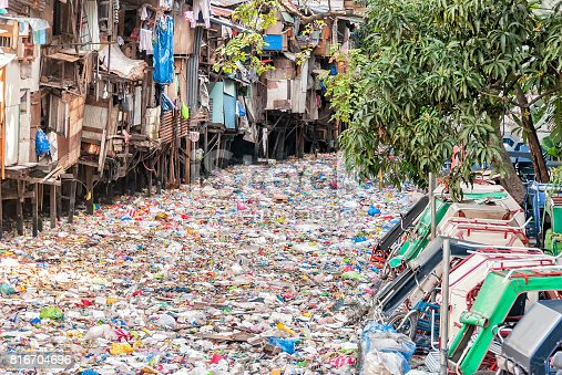 Shanties on stilts standing on garbage-filled river
