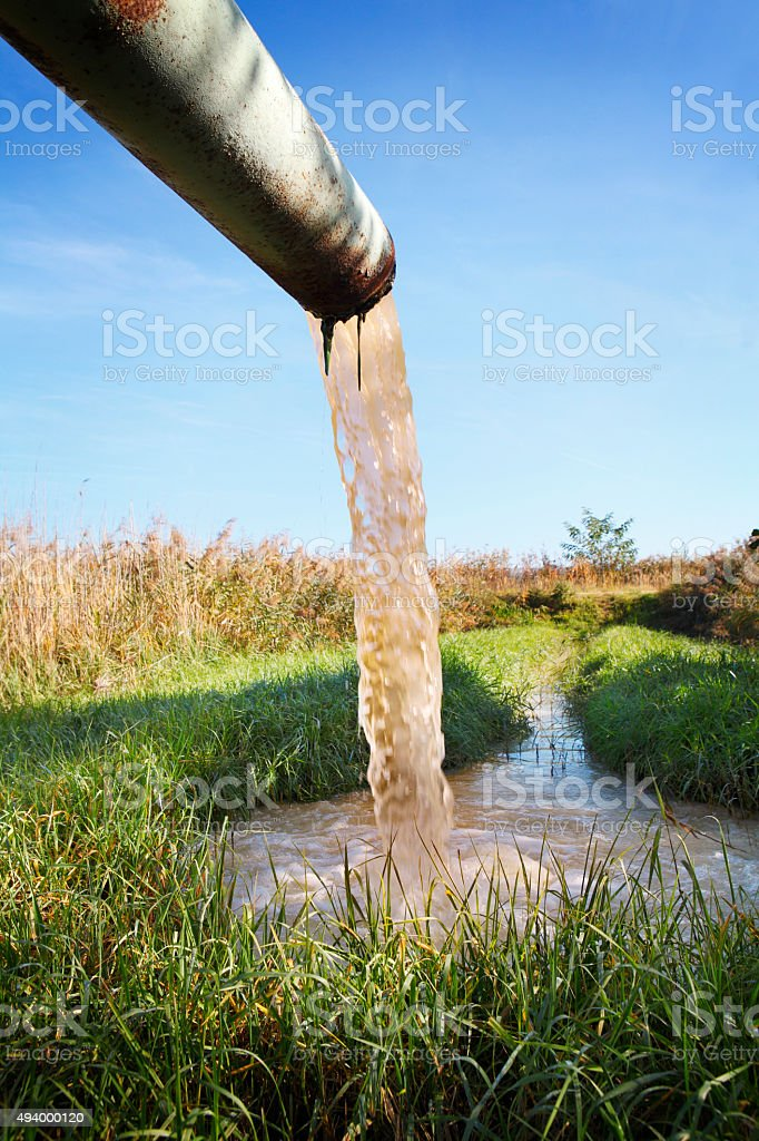 Polluted water flowing into the creek stock photo