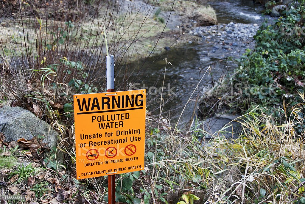 Polluted water sign at creek royalty-free stock photo