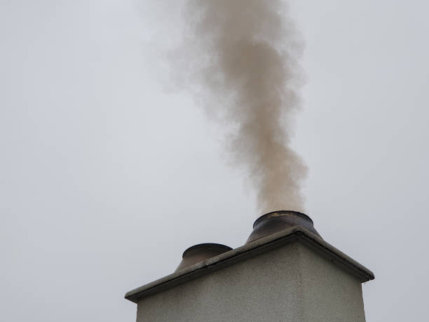 Polluting smoke from chimney in dirty environment stock photo