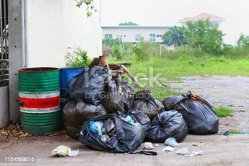 istock Pollution Bin Garbage, Bin bag black Trash beside the fence home office on street, 3R 1154569015