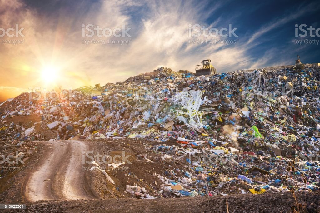 Pollution concept. Garbage pile in trash dump or landfill at sunset. stock photo