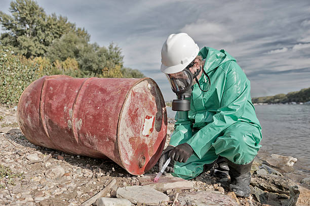 Pollution inspector Environmentalist taking sample at chemical pollution hot-spot environmental cleanup stock pictures, royalty-free photos & images