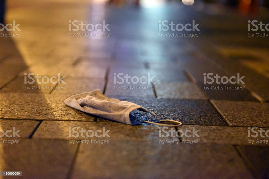 Pollution mask lies on the pavement stock photo