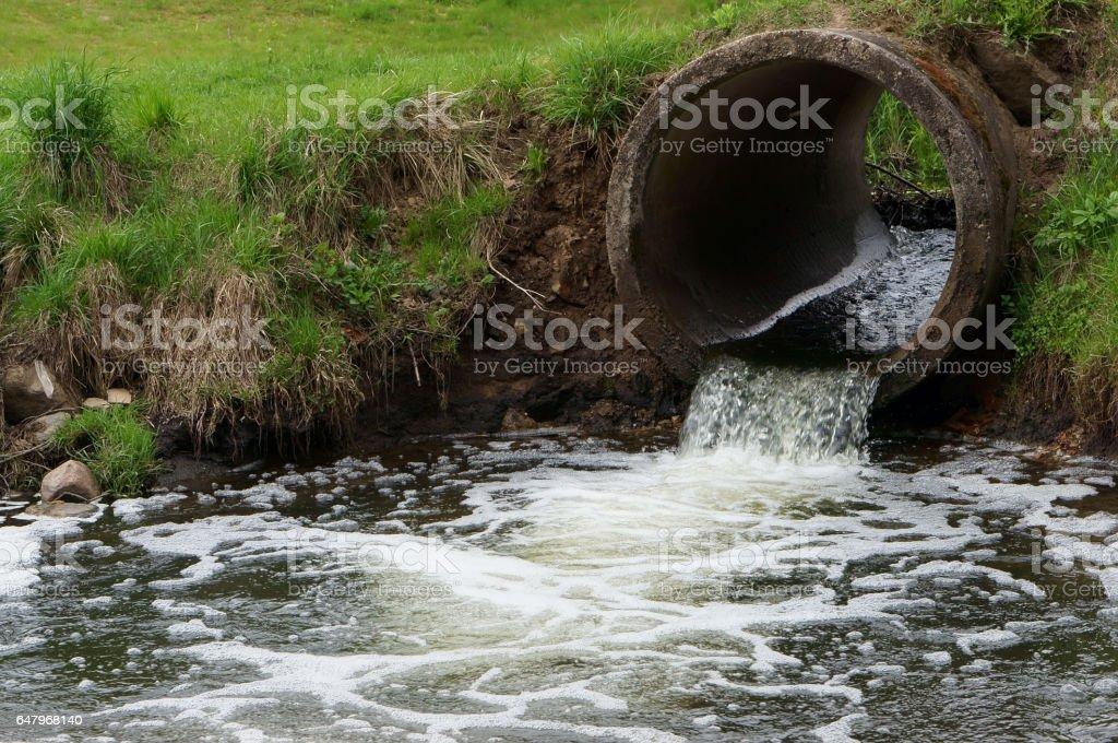 Contaminación del concepto de naturaleza. Flujo de desagües de alcantarillado al río - foto de stock
