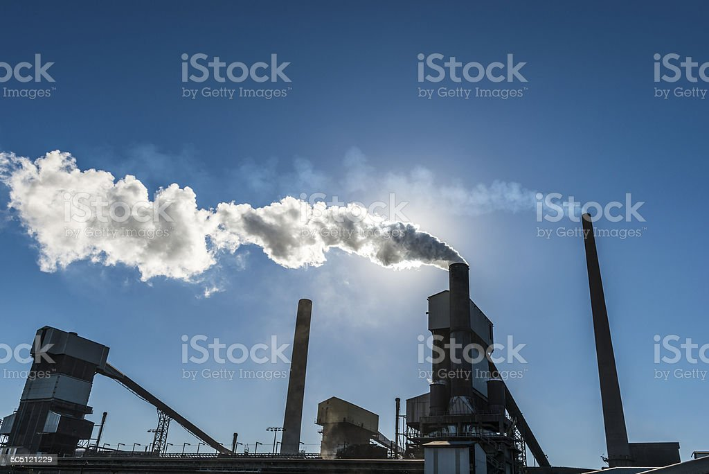 Pollution. Smoke Stacks Silhouette. Steel Industry. Backlit.​​​ foto