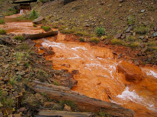 Pollution spewing from an abandoned mine in the Rocky Mountains Orange pollution pouring from the hole of an abandoned mine in the Rocky Mountains.  Opening from an abandoned mine allows the bright orange toxic heavy metals to flow out into running water.  Start of Cement Creek in Silverton, CO that flows into the Animas River. animas river stock pictures, royalty-free photos & images