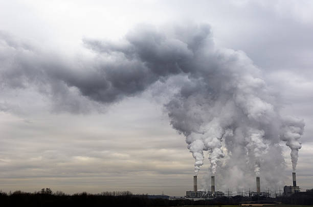 Pollution spilling into the sky from a power plant stock photo