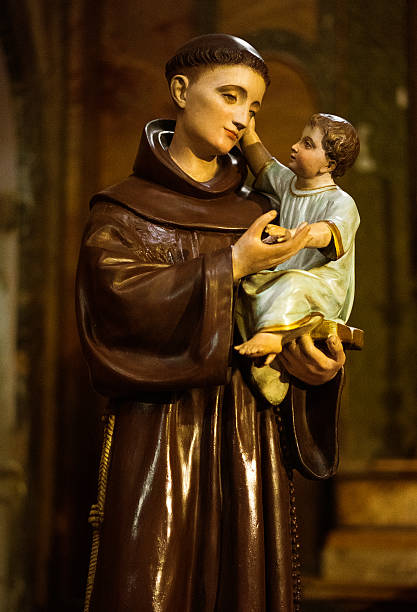polychrome statue of monk and baby polychrome statue of monk and baby on a small roman church, italy st. anthony of padua stock pictures, royalty-free photos & images