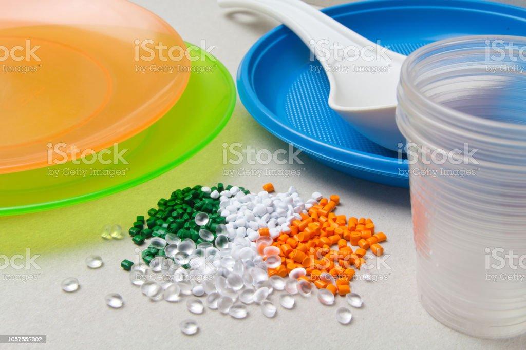 Polyethylene granules and disposable tableware made of polyethylene, polypropylene. BPA FREE concept stock photo