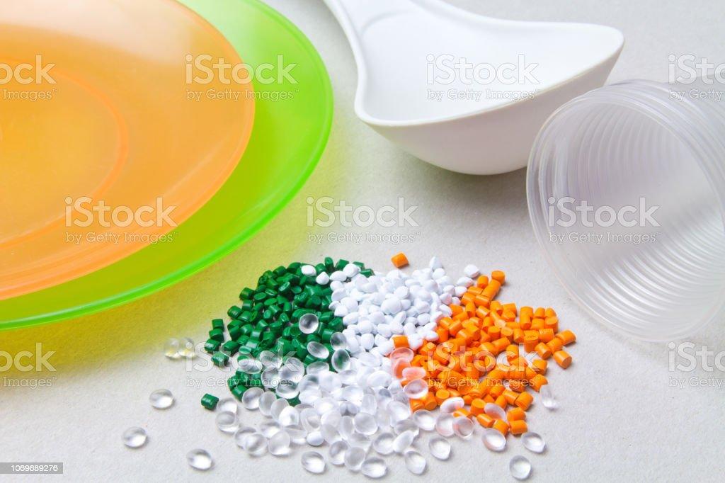 Polyethylene granules and disposable tableware made of polyethylene, polypropylene. BPA FREE stock photo