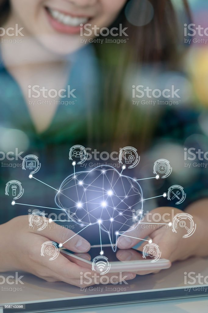 Polygonal brain shape of an artificial intelligence with various icon of smart city Internet of Things Technology over Asian businesswoman hand using the smart mobile phone,AI and business IOT concept stock photo