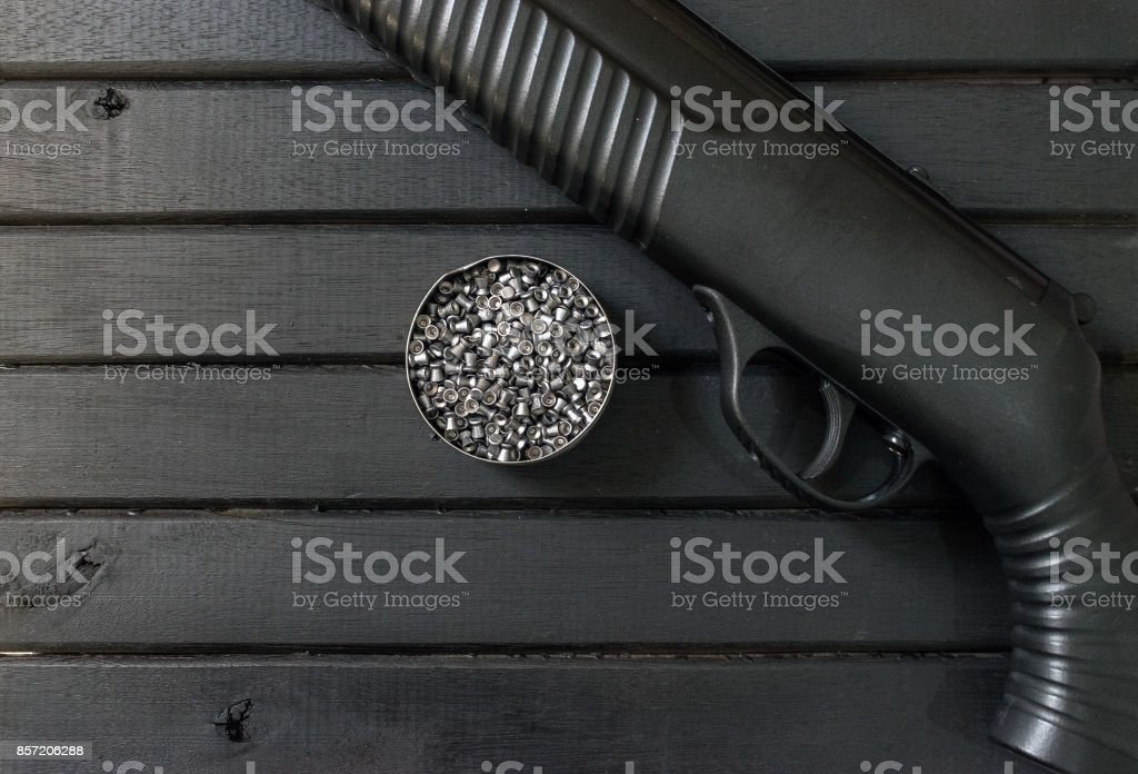Polymer air rifle gun, on a black wooden background, closeup, showing gun body and lead pellets inside a tin can, trigger closeup, and textured grip stock photo